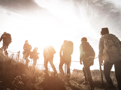 Group of people hiking up a hill, with a sunlit backdrop