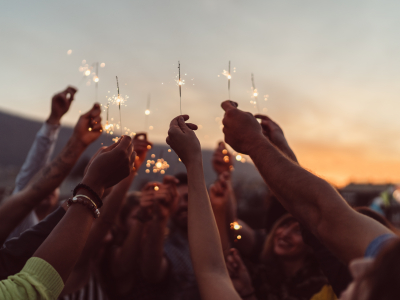 Group of hands held up in air, and all holding lit sparklers.