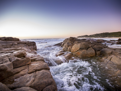 Waves streaming over rocks at sunset