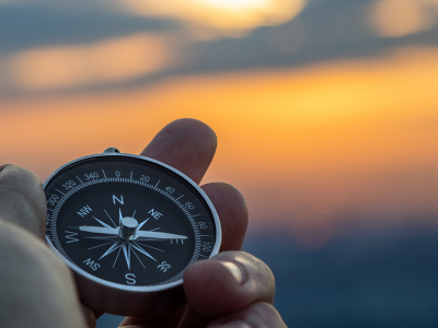 Image of a hand holding a compass with a sunset background