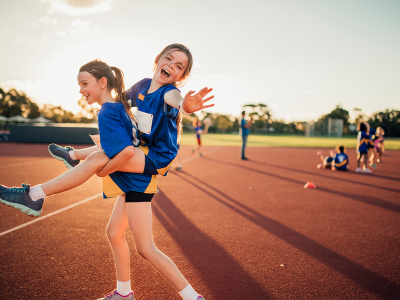 Image of two young girls on athletics track, having fun