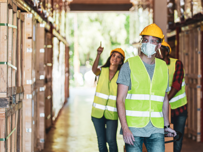 Image of three warehouse workers, wearing hardhats and masks