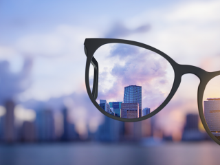 Image of glasses infront of a city skyline, blurry around the glasses